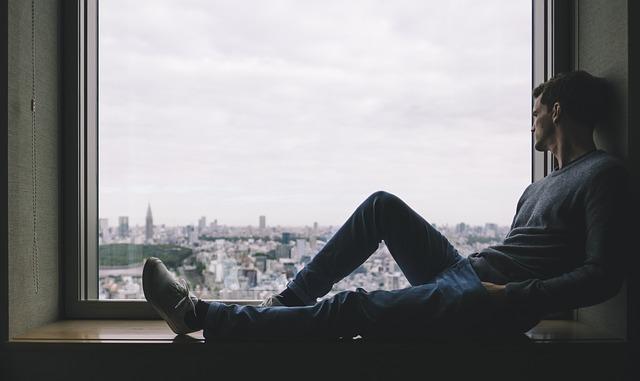 Zamyslený muž sediaci pred veľkým oknom