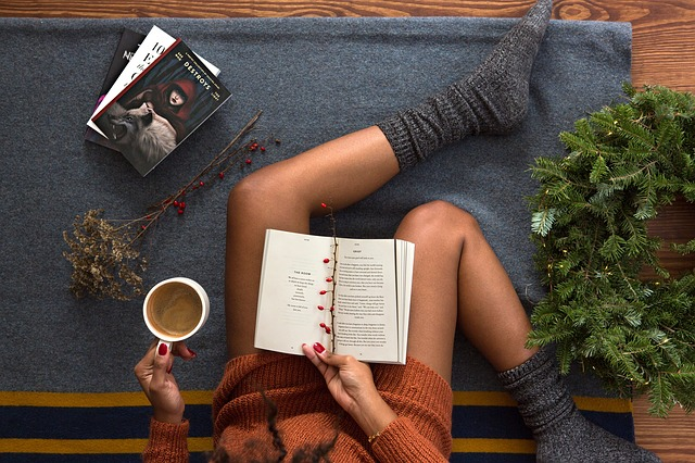 Žena s kávou v ruke číta knihu a sedí vedľa zeleného venca.jpg