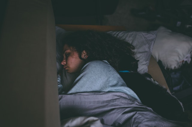 Žena s čiernymi dlhými vlasmi spí v posteli.jpg